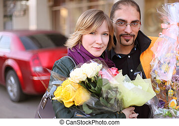 outdoor portrait of man in glasses and beauty blond girl with flower bouquets, looking at camera