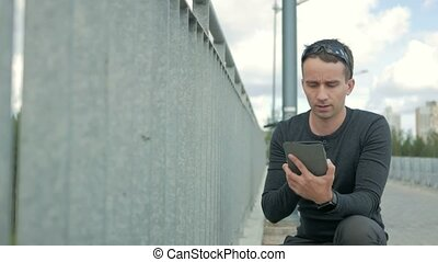 Outdoor portrait of modern young man with digital tablet. Railing of the bridge, near the road and the beautiful blue clouds in the background