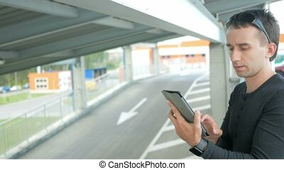 Outdoor portrait of modern young man with digital tablet in the street.