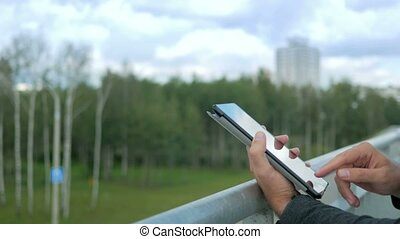Outdoor portrait of modern young man with digital tablet.Against the background of green trees and beautiful blue clouds. Close-up