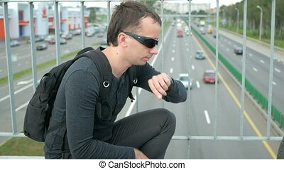 Outdoor portrait of modern young man with smart watch in the street. The man in glasses with backpack sitting on the bridge. Bottom drive cars