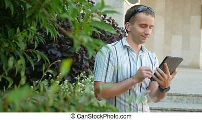 Outdoor portrait of modern young man with digital tablet. Man in sunglasses and jacket. Around a lot of green plants