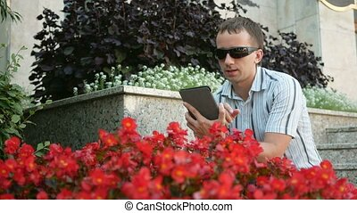 Outdoor portrait of modern young man with digital tablet. Man in sunglasses and jacket. Near a lot of red flowers