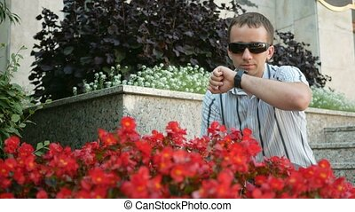 Outdoor portrait of modern young man with smart watch. Man in sunglasses and jacket. Near a lot of red flowers