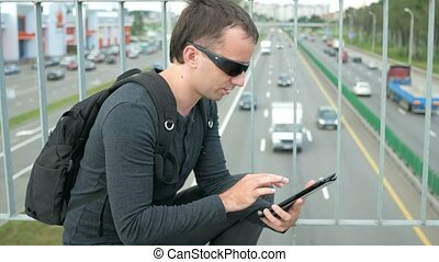 Outdoor portrait of modern young man with digital tablet in the street. The man in glasses with backpack sitting on the bridge. Bottom drive cars