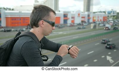 Outdoor portrait of modern young man with smart watch in the street.