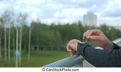 Outdoor portrait of modern young man with smart watch.