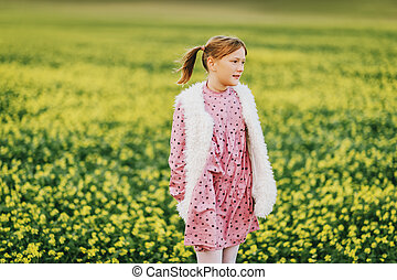 Outdoor portrait of pretty 10 year old girl, wearing pink vintage dress and faux fur bodywarmer, posing in a field