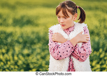 Outdoor portrait of pretty 10 year old girl, wearing pink vintage dress and faux fur bodywarmer, posing in a field, arms crossed