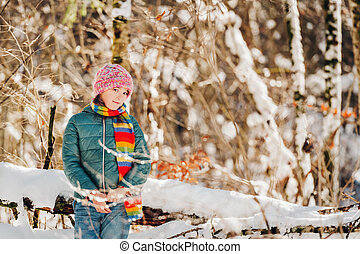 Outdoor portrait of pretty little girl playing in winter forest, wearing colorful scarf and hat
