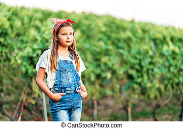 Outdoor portrait of pretty little girl wearing denim overalls and red vintage headband, hands in pockets