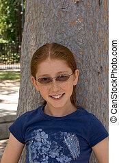 Outdoor portrait of redhead Pre-Adolescent girl in glasses