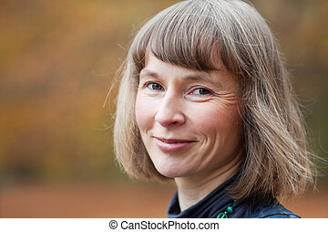 Outdoor portrait of smiling middle aged woman