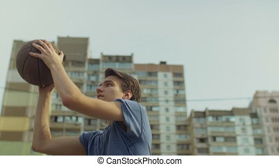 Outdoor portrait of streetball player taking shot