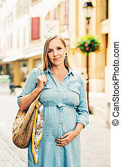 Outdoor portrait of stylish pregnant woman posing in the city, wearing denim dress