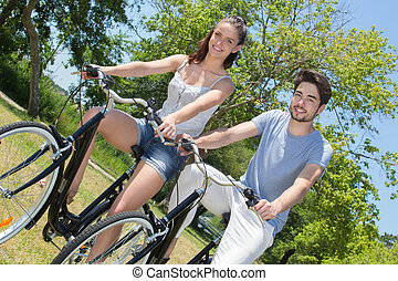 outdoor portrait of teenage couple riding bicycles in nature