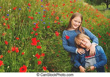 Outdoor portrait of two cute kids playing in poppy field
