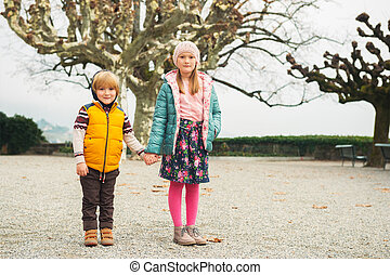 Outdoor portrait of two kids, little girl and her brother, wearing warm colorful jackets
