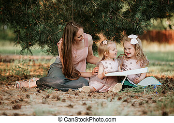 Outdoor portrait of two little girl is reading a book on the grass with mother. She has a look of pleasure and she looked very relaxed in her mother's arms.