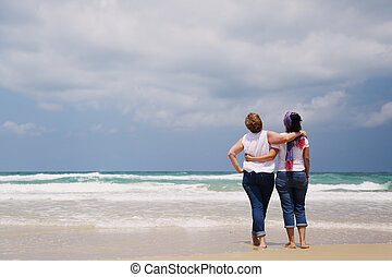 Outdoor portrait of two women standing on the beach