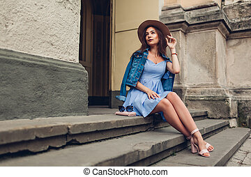 Outdoor portrait of young beautiful fashionable woman wearing stylish accessories. Girl sitting on stairs in city