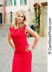 Outdoor portrait of young blond woman wearing red dress