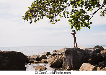 Outdoor portrait of young elegant fit woman standing on a rock near tropical beach with sea. Sports girl in bikini enjoy nature summer vacation, Thailand sea