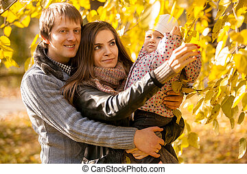 family having fun at autumn park with small daughter