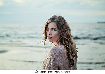 Outdoor Portrait of Young Woman Looking at Camera on Natural Background with Copy Space