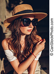Outdoor portrait of young woman wearing vintage outfit and accessories. Girl in glasses and hat sitting on stairs