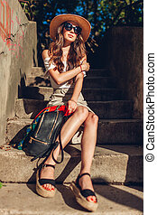 Outdoor portrait of young woman wearing vintage outfit and accessories. Girl in glasses, hat with bag sitting on stairs