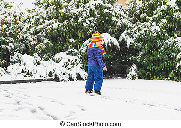Outdoor portrait young 4 year old boy wearing blue jacket, colourful set of handmade knitted hat and scarf, enjoying winter time