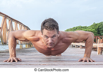 Outdoor push up workout - Front low angle of muscular...