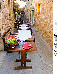 Outdoor restaurant on a narrow pedestrian street in Hvar, ...
