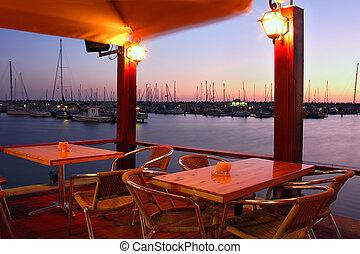 Outdoor restaurant on marina at evening. - Outdoor ...