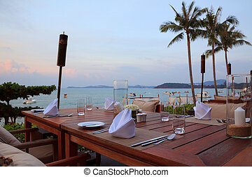 Outdoor restaurant tables, dinner setting at the beach on sunset