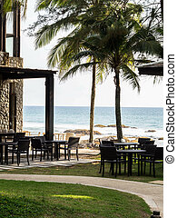 Outdoor restaurant with tables and chairs in the open space under the palm trees against the blue calm sea and sandy beach. Copy space
