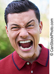 Outdoor Shot Of Angry Young Man Shouting At Camera