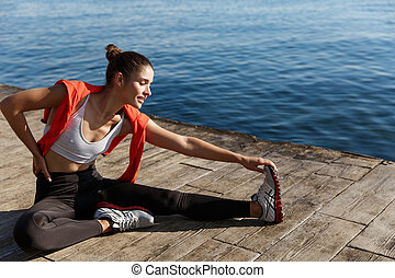 Outdoor shot of beautiful fitness woman working out near sea. Sportswoman sitting on pier and stretching legs