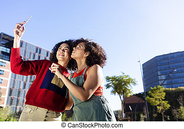 Outdoor shot of two multiracial young women having fun on city street and taking selfie.