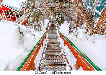Outdoor stairway with grated metal treads in a snowy mountain town in winter