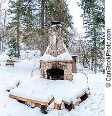 Outdoor stone fireplace in a beautiful landscape of snowy mountain in winter
