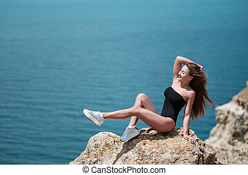 Outdoor summer beach tropic portrait of young sexy sensual tanned sport woman posing on the sea in sunny weather and have fun in vacation time
