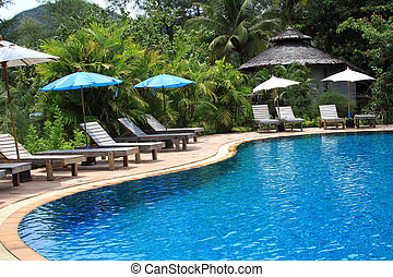 Outdoor swimming pool and wooden chairs in Thailand