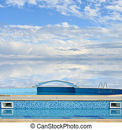 Outdoor swimming pool on a background of sky and sea