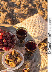 Outdoor table arrangement with glasses of wine, dried fruits and