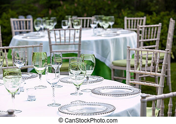 Outdoor tables set for fine dining during a wedding in a garden.