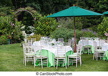 Outdoor tables set for fine dining during a wedding in a garden with umbrellas