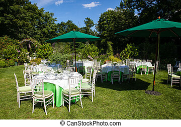 Outdoor tables set for fine dining during a wedding.