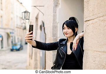 Outdoor urban shot of beautiful sexy young Asian smiling woman in black leather jacket, making self portrait on smartphone, posing at old city street. Selfie, people, lifestyle concept.